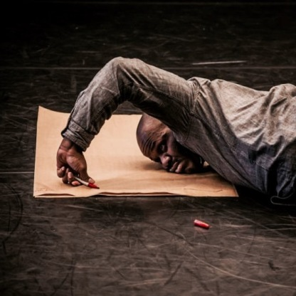 large black male in dark clothing lying face down on top of a piece of light brown butcher paper, that is on the floor. Only the upper half of the body is visible. the black male is using one arm to write on the paper with a red marker. The visible arm is bent at a slight right angle with the hand in a fisted position while writing. The marker's cap lies on the floor off of the paper.