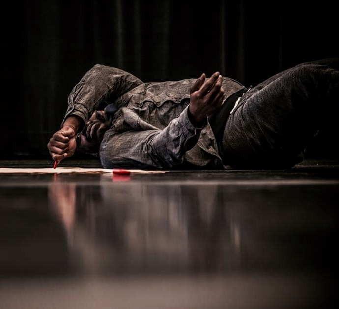 Image of large black male in dark clothing lying on the side, while on top of a piece of light brown butcher paper that is on the floor. The body is in a twisted position visible from the knees up. One arm partially covers the face, holding a red marker that is pressed on the paper. The other arm that is closer to the floor slightly gestures with hand reaching away from the body. The marker's cap lies on the floor off of the paper. There is an mirrored impression of the body reflected on the surface of the shiny floor